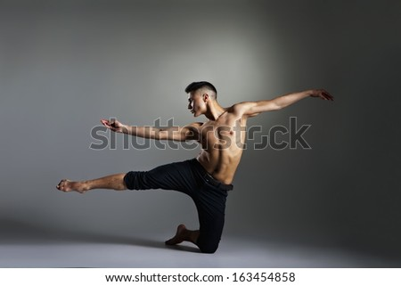 Young and stylish modern ballet dancer on grey background - stock photo