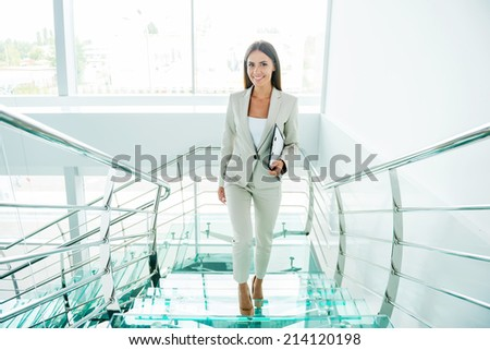 Young and successful. Beautiful young businesswoman in formalwear moving up by staircase and smiling - stock photo