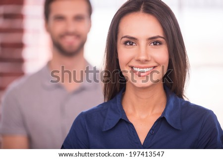 Young and successful. Beautiful young woman looking at camera and smiling while man standing behind her