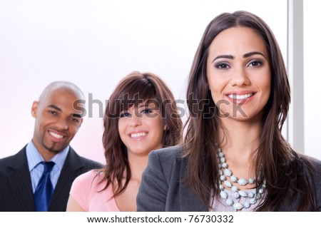 Young and successful business team, three smiling people of different races. - stock photo