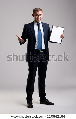 Young and successful businessman holding a clipboard - stock photo