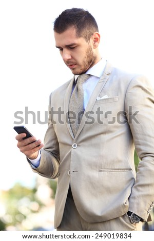 Young and successful businessman is reading a message on his smartphone - stock photo