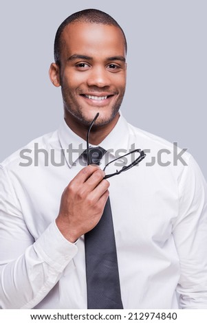Young and successful. Confident young African man in shirt and tie holding eyeglasses and smiling while standing against grey background  - stock photo