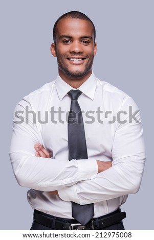 Young and successful. Confident young African man in shirt and tie keeping arms crossed and smiling while standing against grey background  - stock photo