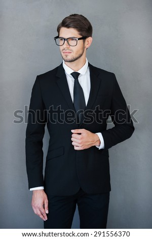 Young and successful. Confident young businessman adjusting his jacket and looking away while standing against grey background - stock photo