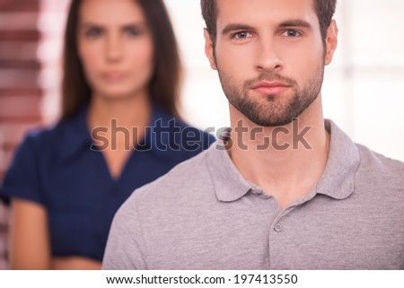 Young and successful. Confident young man looking at camera while woman standing behind him and keeping arms crossed - stock photo