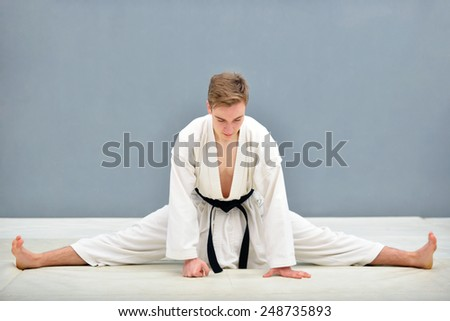 young and successful karate stretching before a workout