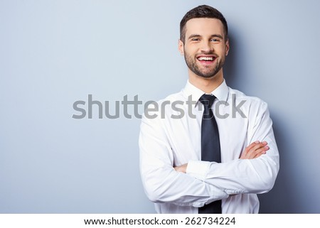 Young and successful. Portrait of handsome young man in shirt and tie keeping arms crossed and smiling while standing against grey background - stock photo