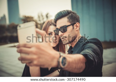 Young and trendy man and woman models walks of the modern street. Fashion Style Selfie photo. - stock photo