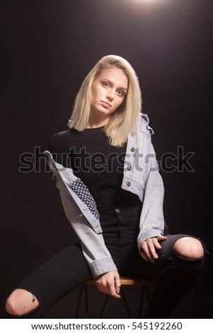 young androgynous adult girl woman 19 fashion model posing. Sitting wearing casual clothes, denim jacket, black shirt, black jeans. Studio black background.