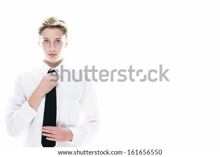 young androgynous woman correcting her black tie on white background - stock photo