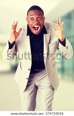 Young angry black businessman screaming - stock photo
