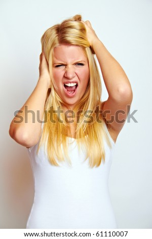 young angry blond woman is screaming - stock photo