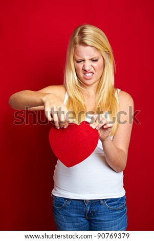 young angry blond woman with a heart in her hands - stock photo