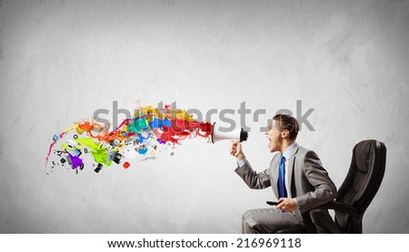 Young angry businessman sitting on chair and screaming in megaphone - stock photo