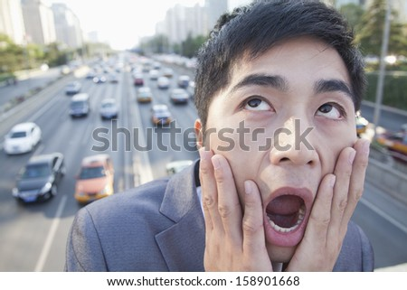 Young angry businessman yelling over freeway - stock photo