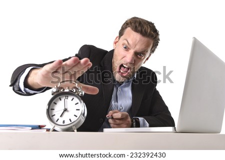 young angry exploited businessman at office desk stressed and frustrated with computer laptop and alarm clock in out of time, project deadline time concept, stress, overwork and frustration - stock photo