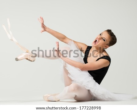 Young angry fed up ballerina dancer sitting on a floor