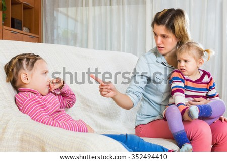Young angry mother sitting on sofa and scolding little daughter - stock photo