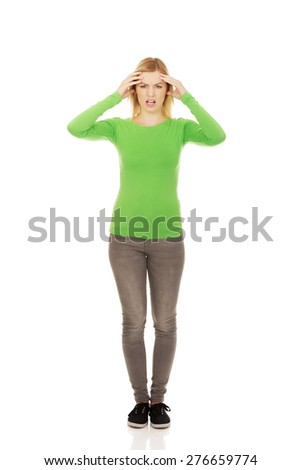 Young angry woman holding her head. - stock photo