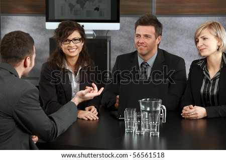 Young applicant explaining to panel of happy businesspeople during job interview in office. - stock photo