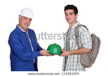 young apprentice and  mature workmate in jumpsuit - stock photo