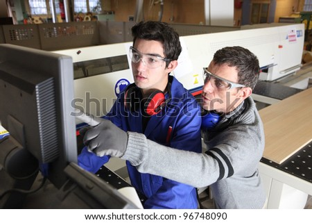 young apprentice in industry sector with tutor - stock photo