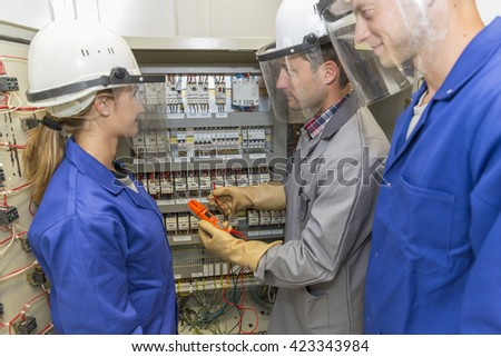 young apprentice with electrician professional - stock photo