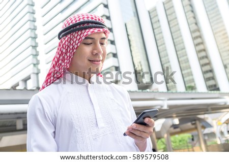 Young Arab businessman using mobile phone while walking in the city. business travel and mobile roaming concepts.