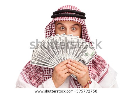 Young Arab hiding his face behind a stack of money isolated on white background - stock photo