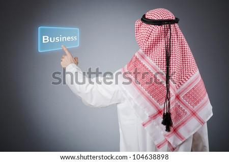Young arab pressing virtual buttons - stock photo