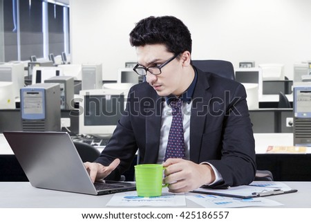 Young Arabian businessman working in the office seriously while holding a cup of coffee and using laptop