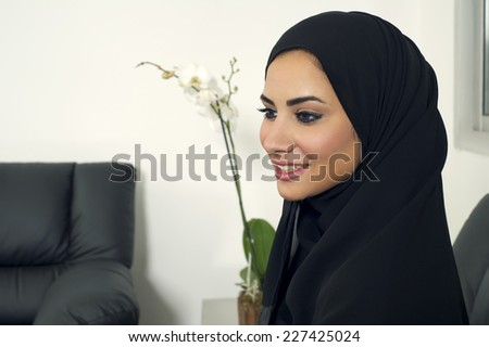young arabian businesswoman indoors, Arabian Businesswoman wearing Hijab in office - stock photo