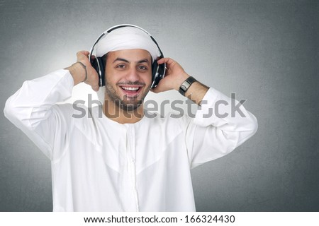 Young Arabian man listening to music using headphones isolated