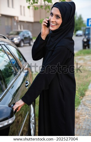 Young Arabian Woman Getting In The Car While Speaking On Smart Phone - stock photo