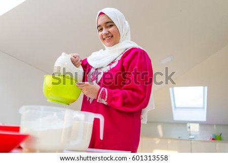 Young Arabic Muslim mother and happy playful son making muffins in kitchen