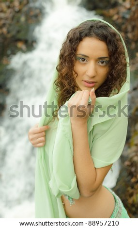 Young arabic woman near the waterfall - stock photo