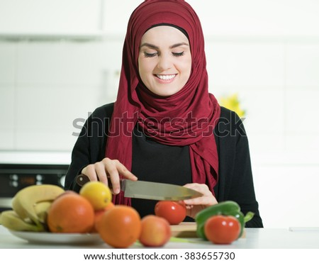 Young Arabic woman preparing meal in the kitchen.  - stock photo