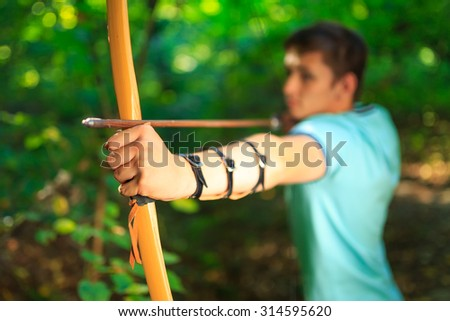 Young archer on training in forest. - stock photo