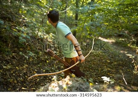 Young archer on training in forest.
