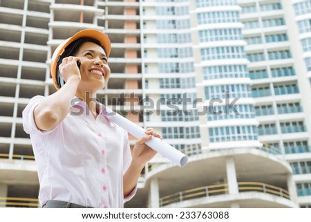 Young arching with a blueprint talking on the phone - stock photo