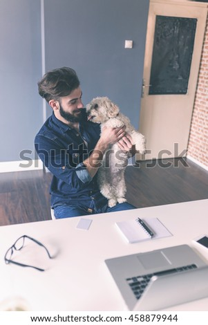 Young architect brings his dog to work - stock photo