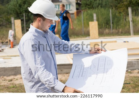 Young architect checking a structural drawing or blueprint as he stands on the building site of a new house - stock photo