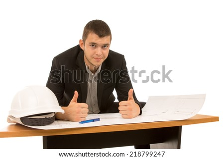 Young architect giving a thumbs up of success as he sits working on a blueprint at a small wooden table with his hardhat, isolated on white