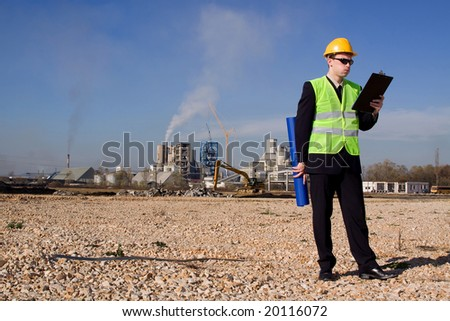 young architect in front of industrial construction site
