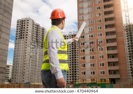 Young architect in hardhat and safety vest pointing building with rolled blueprints