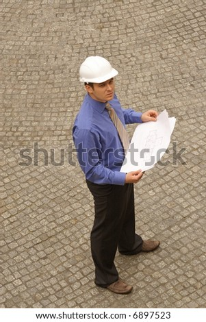 Young architect in hardhat standing on pavement with blueprints - stock photo