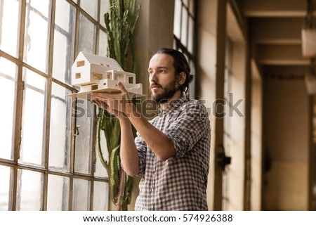 Young architect is looking on the new model in the old industrial space with big factory windows. Man is standing in front of window and holding small model of the house. Color toned image.
