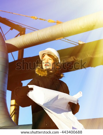 Young architect looking at blueprint in front of construction site against blue sky                 - stock photo