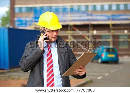 young architect or inspector talk over his mobile phone, outdoor shoot with blurred office building as background - stock photo